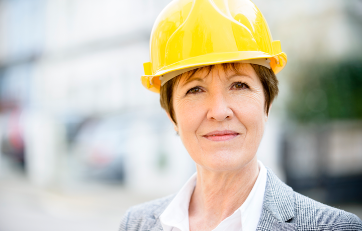 Middle aged woman looking at the camera wearing a yellow hard hat