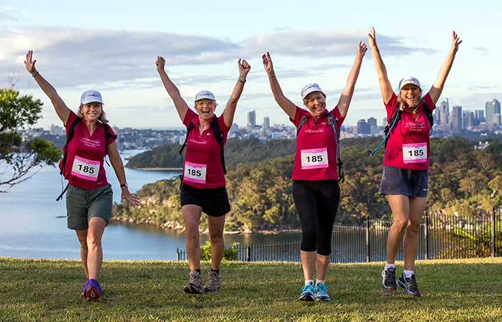 Four women walking enthusiastically in front of Sydney Harbour