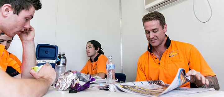 Tradies sitting in the tea room reading the paper