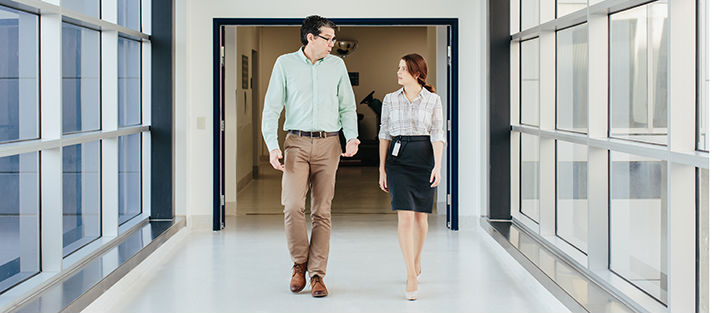Man and women walking down hallway