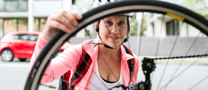 Woman looking through bicycle wheel spokes